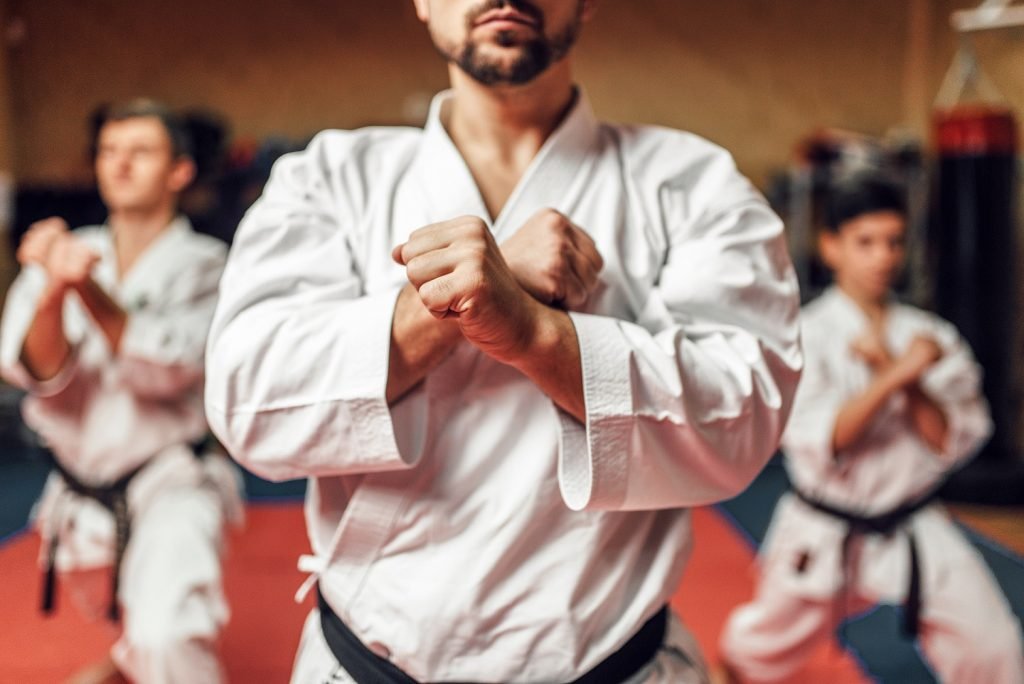 Martial arts karate fighters, master and his disciples in white kimono and black belts hone their skills, fight training in action, workout in gym